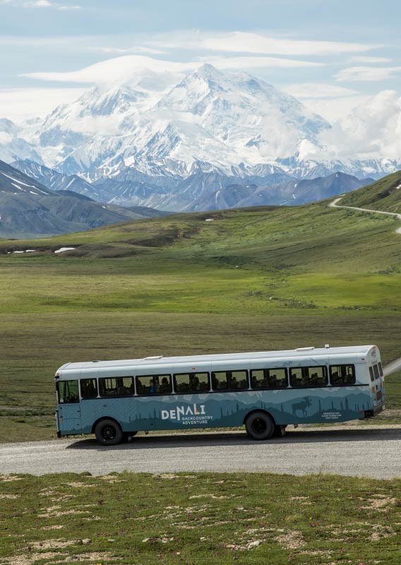A bus drives along a road, above a tundra landscape and mountains in the distance.