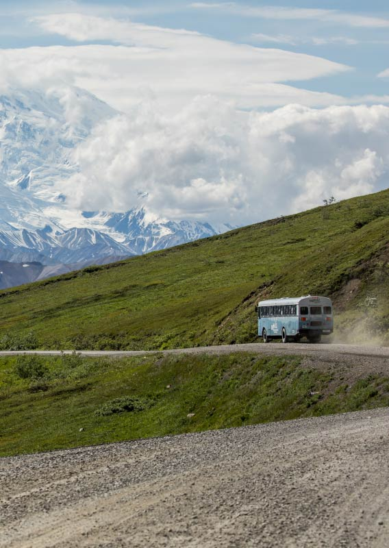 A blue tour bus drives along a gravel road through green hills towards high snowy mountains.