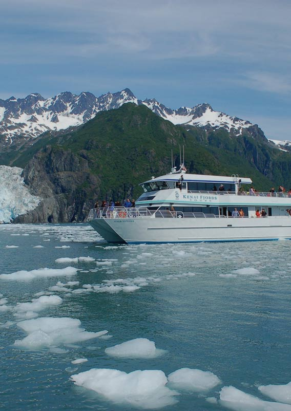 A boat approaches a glacier by the sea.