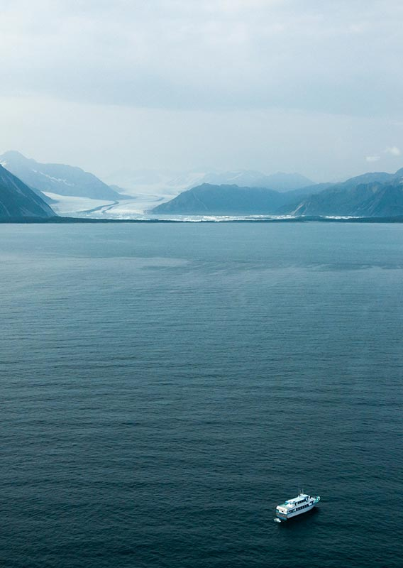 A boat cruises on the sea between forested mountains and a glacier in the distance.