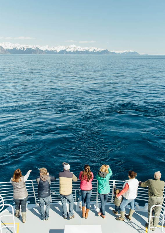 People stand at front of Kenai Fjords Tours boat on a sunny day