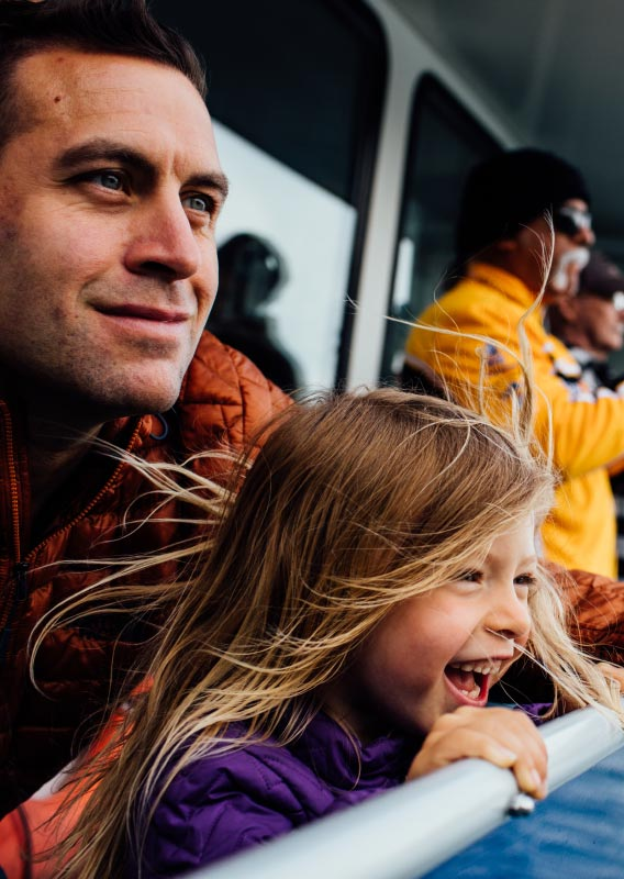 A child smile excitedly with her father on a boat deck.
