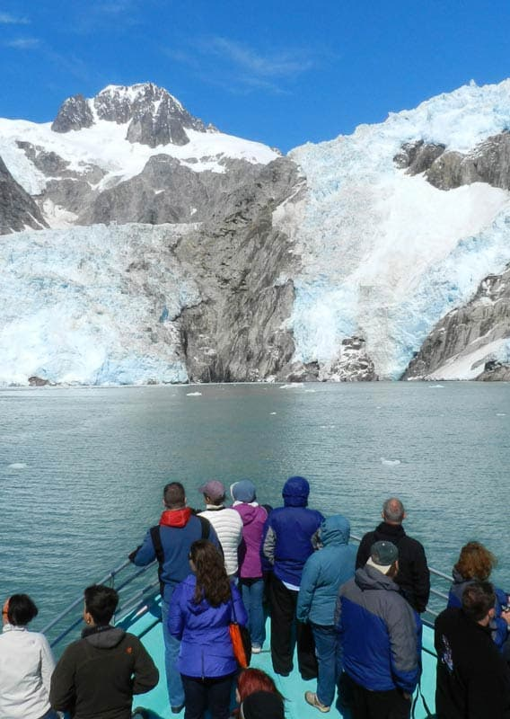 A group of people stand at the front of a boat, looking out towards a glacier.