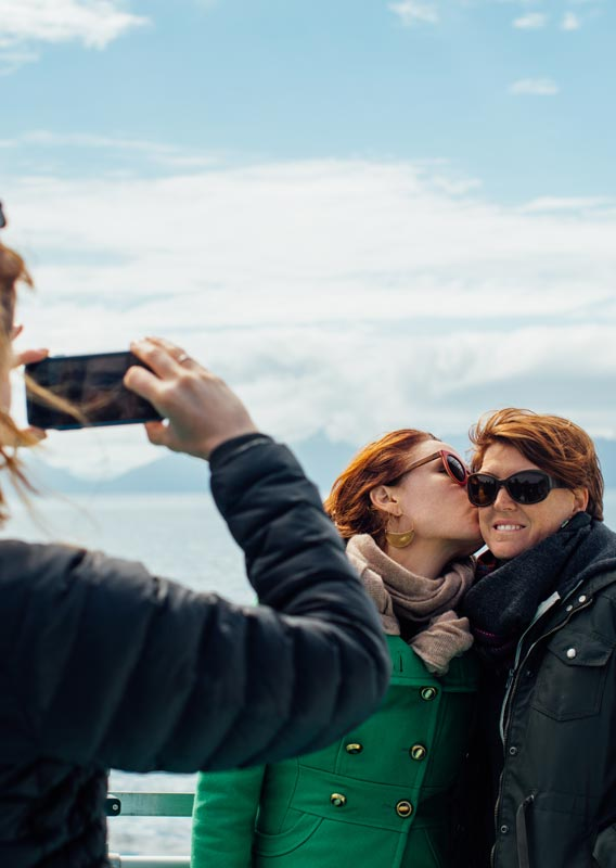 Mother and daughter pose on Kenai Fjords Tour boat while someone takes a photo of them