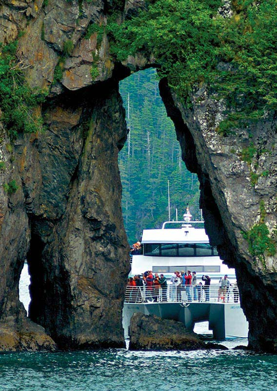 A boat settles in behind towering pillars of mossy, tree-covered rock.
