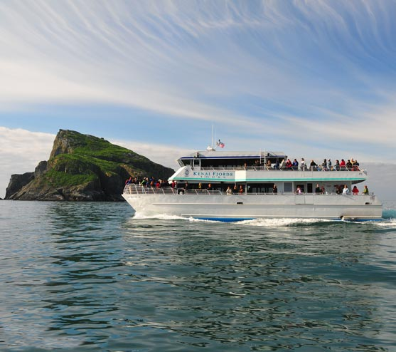 A boat with many people on board passes by an island