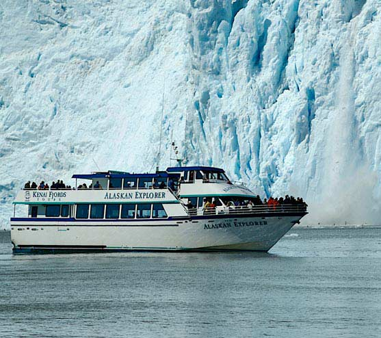 A boat moves alongside the wall of a glacier, as a piece of ice crashes into the water.