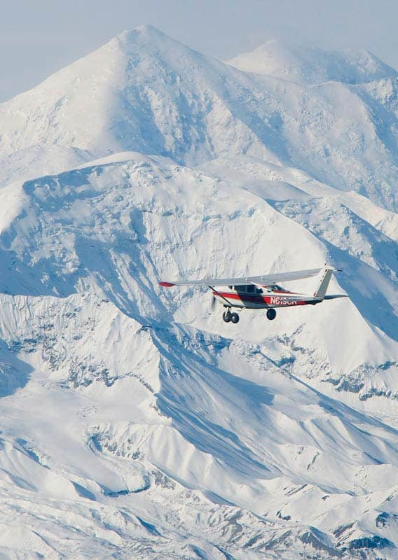 A propeller plane flies past snow-covered mountains
