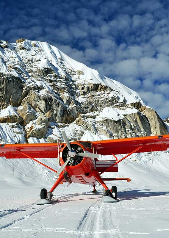 Red Airplane parked on snow beneath a snowy mountain