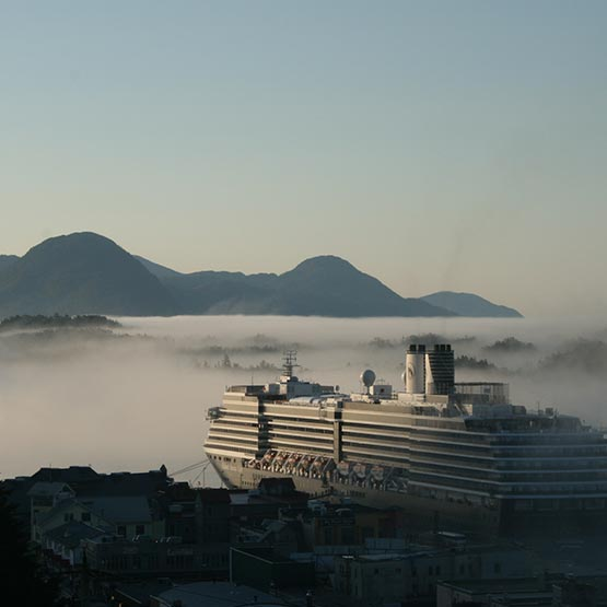 A cruise ship docked at a port with fog above the sea and land.