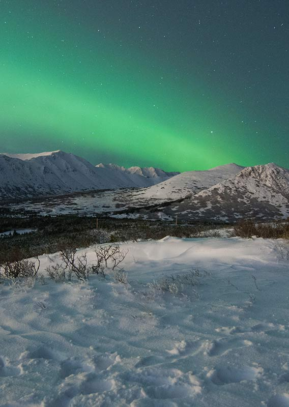 Northern Lights over snowy Alaskan mountains in winter