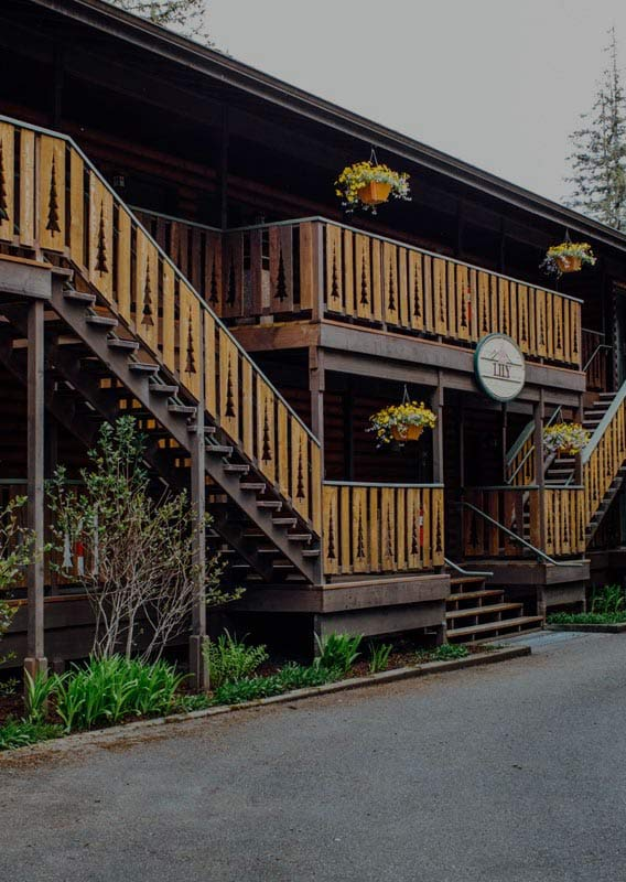 A wooden lodge with rustic decorative railings on staircases and balconies