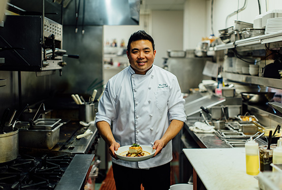 Chef Wes Choy holding a plate of food in a restaurant kitchen.