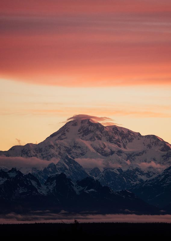 Denali, a tall mountain, rises above a later of clouds below a red sky.