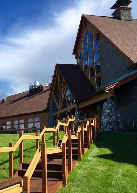 Wooden stairs lead to an A-frame lodge through a green l awn