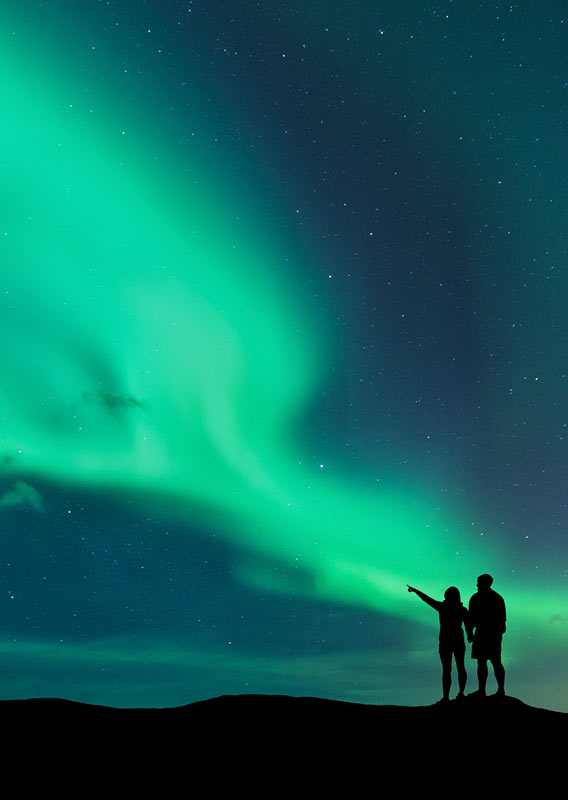 Two people stand silhouetted under impressive display of northern lights and starry skies
