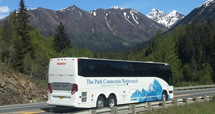A motorcoach drives on a road beside lightly-snowy mountainsides.