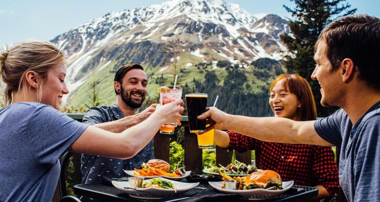 Four friends raise their glasses in cheers on a patio with mountains behind