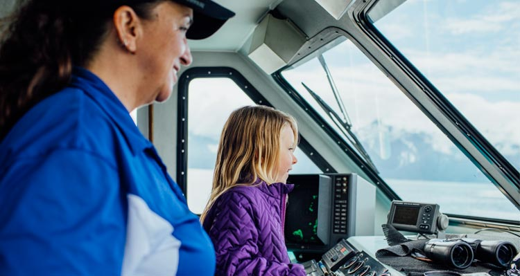 A child stands at a boat's helm with the captain