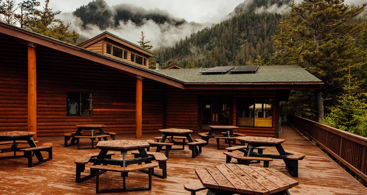 The deck at Kenai Fjords Wilderness Lodge with recently rained-on picnic tables