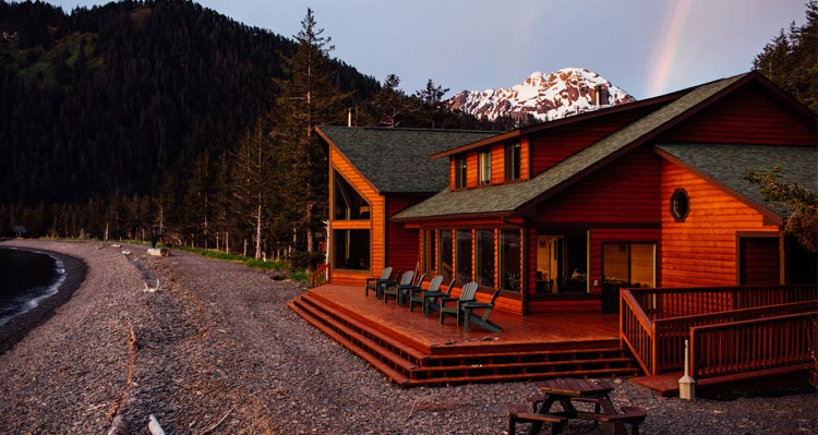 A view of the Kenai Fjords Wilderness Lodge at sunset with a rainbow formed behind it