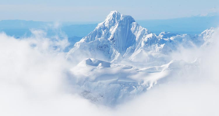 A snow-covered mountain peak pokes out above clouds.