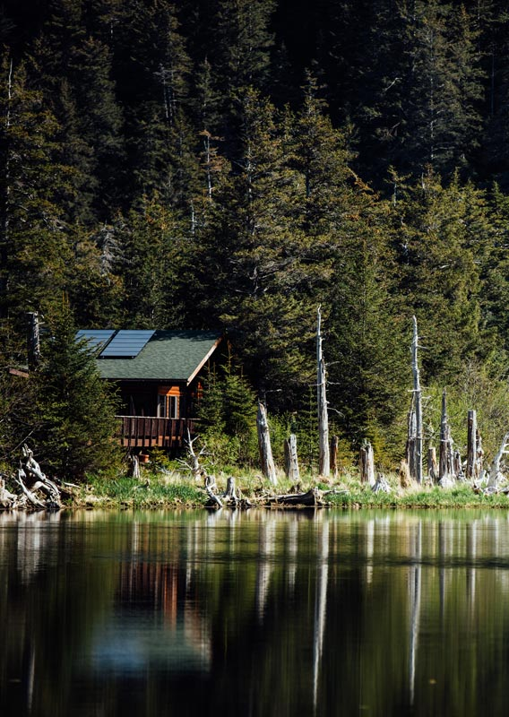 A lodge nestled among trees by calm waters