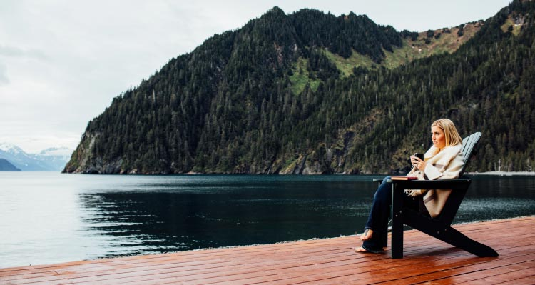 A woman sits in an Adirondack chair on a dock, looking out to ocean and tree-covered cliffsides.
