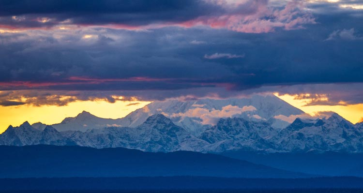 A view of Denali with glowing sunshine and dark clouds above.