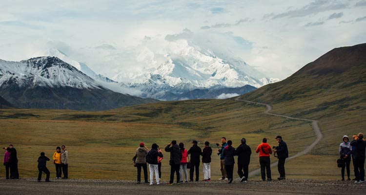 A crowd of people take photos of Denali from the Denali Park Road.