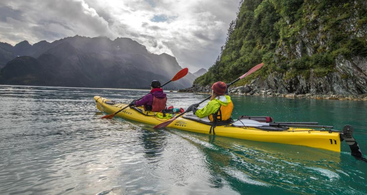 Two kayakers paddle around plant-covered, rocky cliffs.