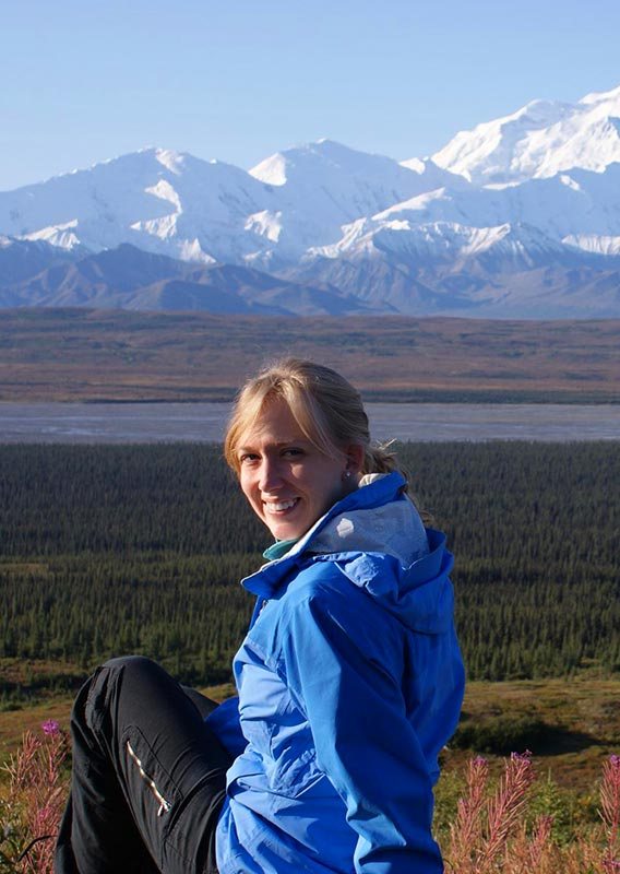 A person sits among fireweed, with a big view of Denali.