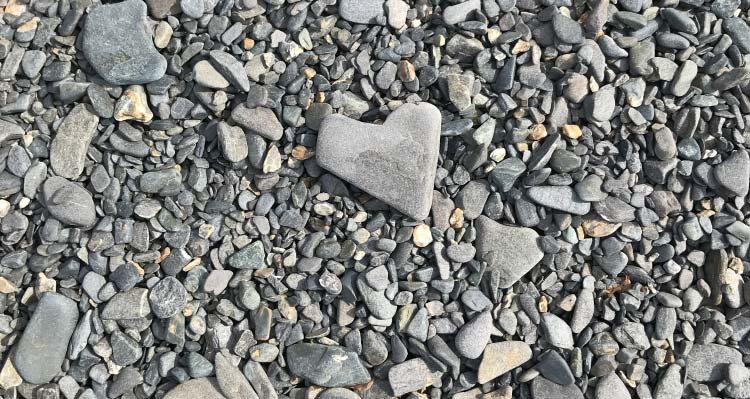 A heart-shaped rock among small pebbles.