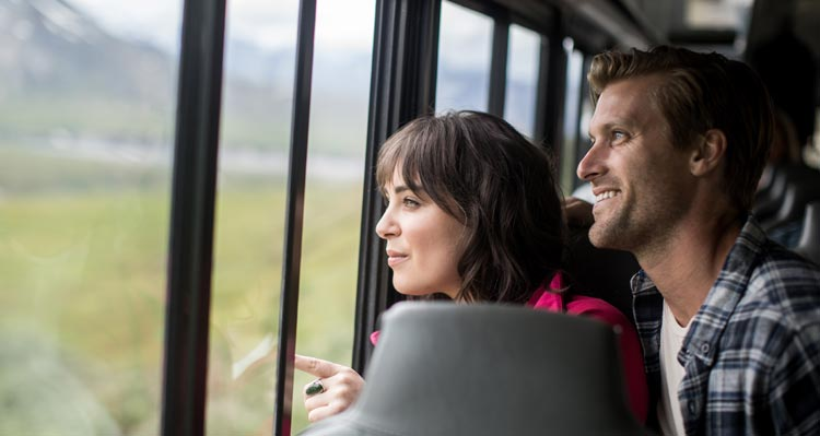 Two people look out a window of a bus.