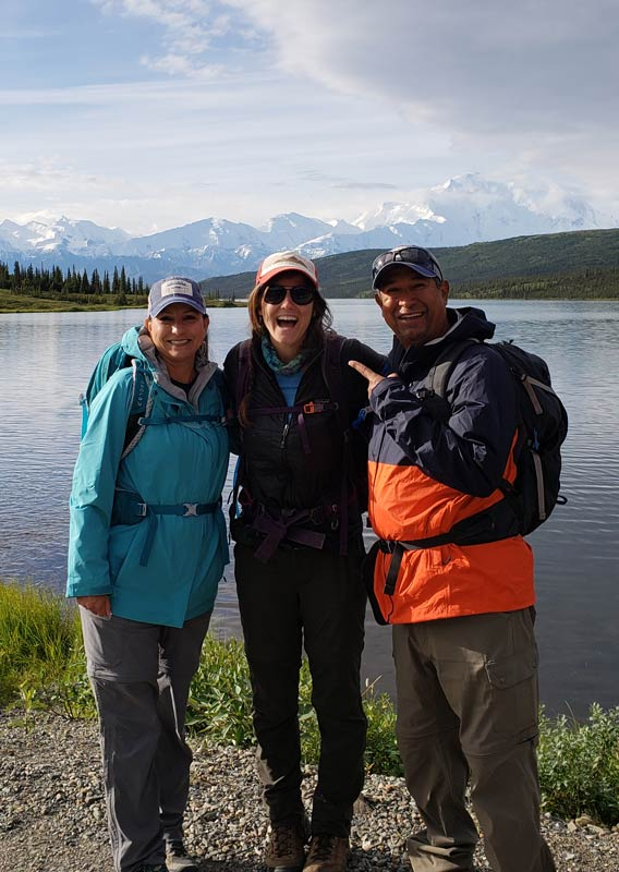Three people stand and smile in front of a crisp lake in a tundra and mountain landscape.