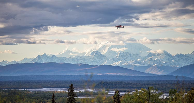 A small plane flies above an open Alaska landscape with Denali in the background.