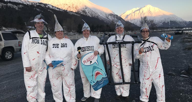 A group of friends, dressed as sharks, ready for a polar plunge.