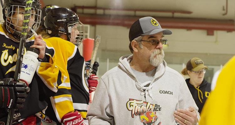 Martin Brewer coaches a team of hockey players.
