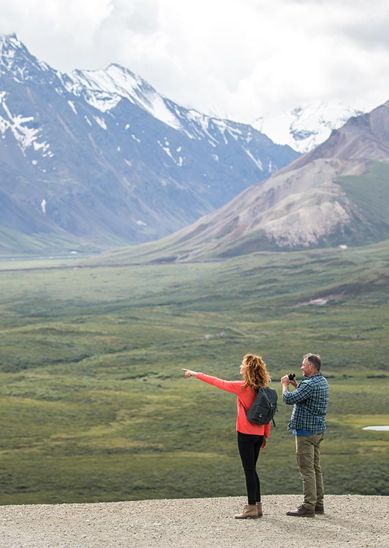 Two people overlook a a river and tundra landscape.