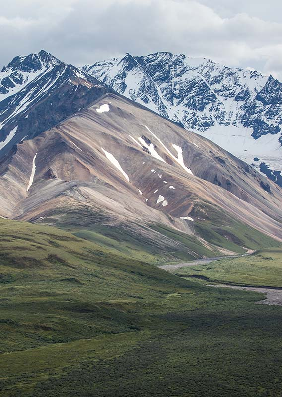 Mountains rise above a tundra valley and river.