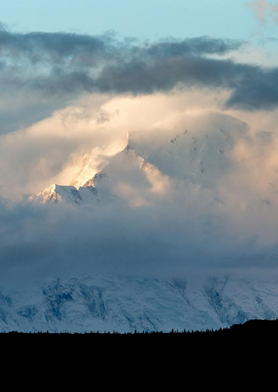 Denali, a tall snow-covered mountain between clouds.