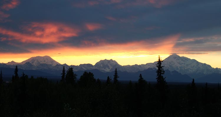 A view of the Alaska Range mountains under a red sky and sunset