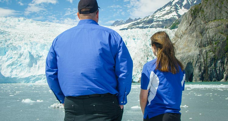 Two people look at a large glacier from a boat.