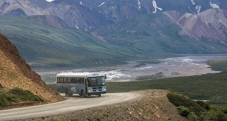 A bus rounds a corner along a mountainside road.
