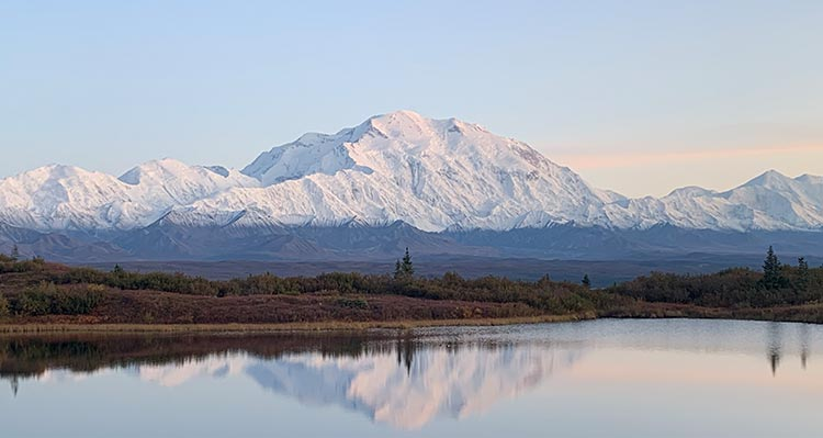 A landscape view of Denali, a tall mountain rising above other snow-covered mountains and a tundra landscape.