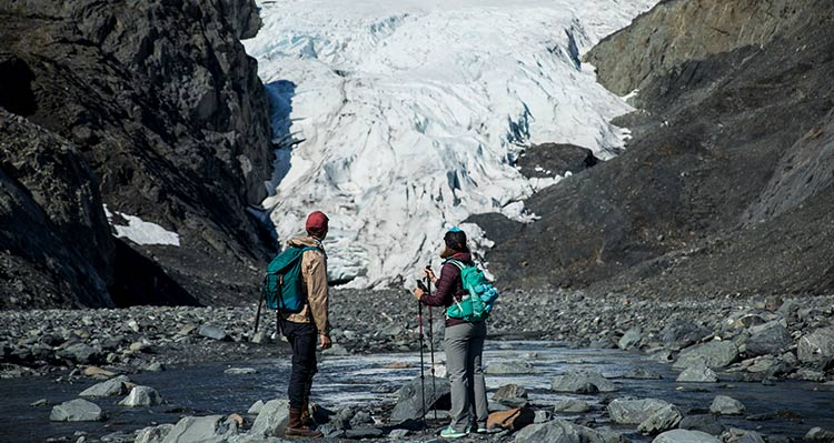 Two hikers look towards a glacier.