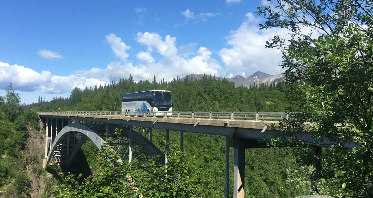 A motorcoach drives on a bridge between forests and mountains.