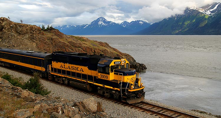 An Alaska Railroad train travels along the water