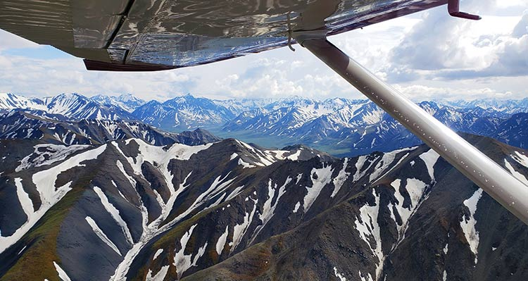A view from a small plane above snow-covered mountains.