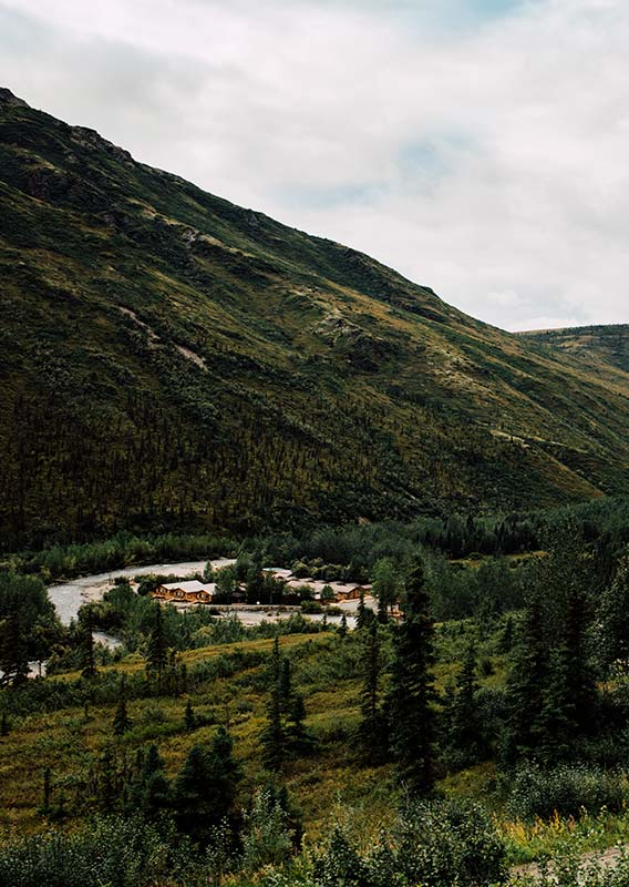 An aerial view of the Denali Backcountry Lodge, nestled alongside a river below forested mountains